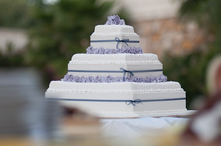 Hranatý třípatrový dort ozdobený stuhou.