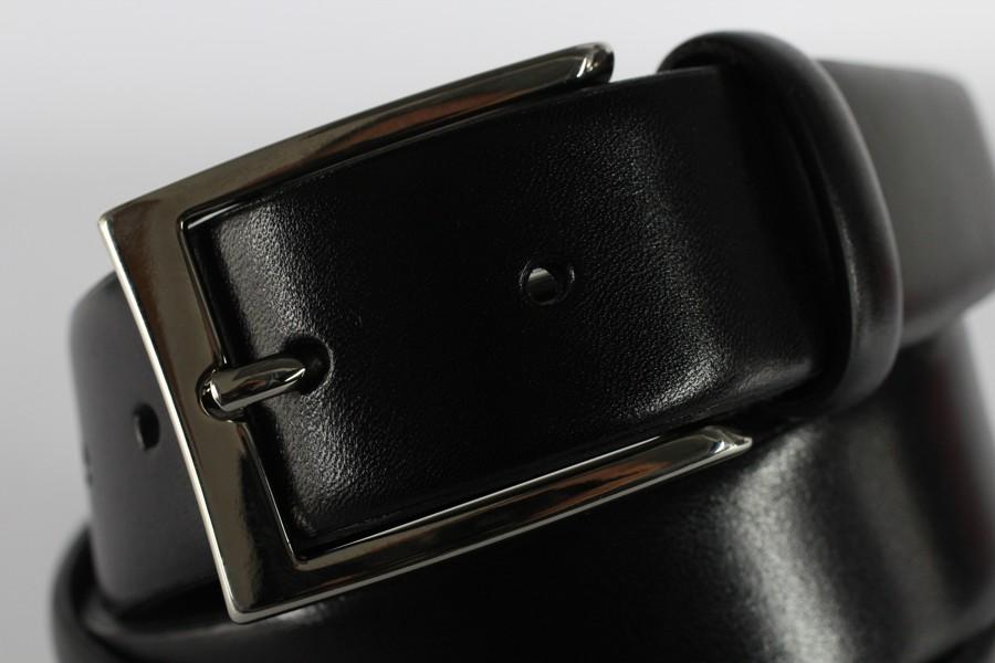 Lesklý černý kožený pásek se vždy zapíná na třetí dírku.