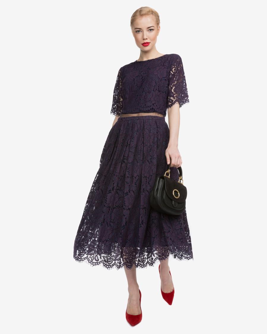 35f9621a6c9 Temně modré krajkové šaty do půli lýtek s rukávy a rudými doplňky.