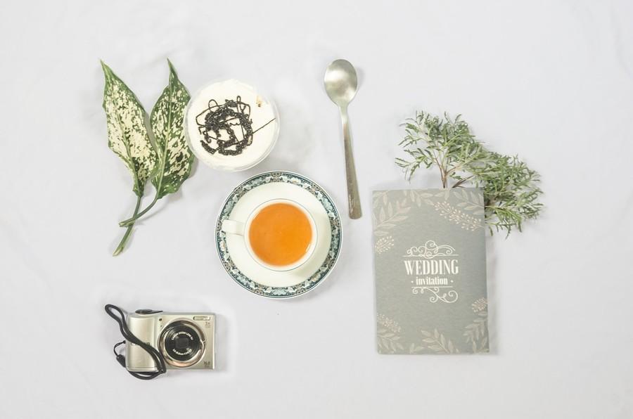 Flatlay šedivého svatebního oznámení, čaje a fotoaparátu.
