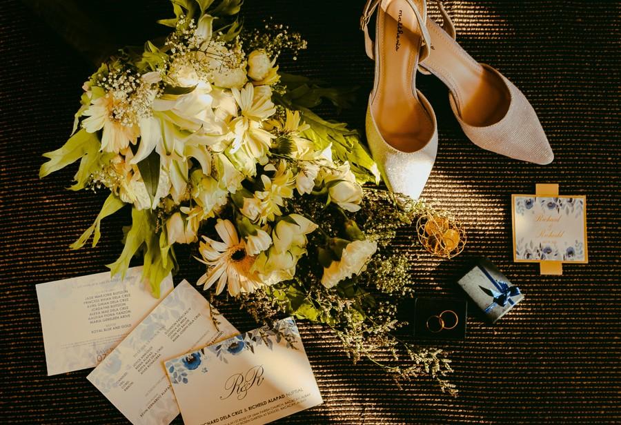 Zátiší se svatebním oznámením, lodičkami a svatebními květinami.