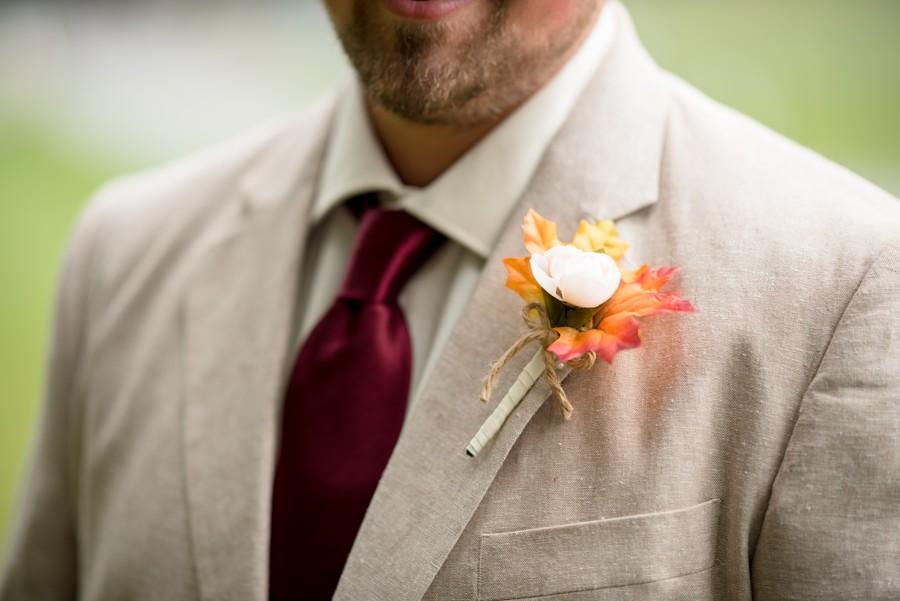 Oblek v béžové barvě s bordó kravatou.