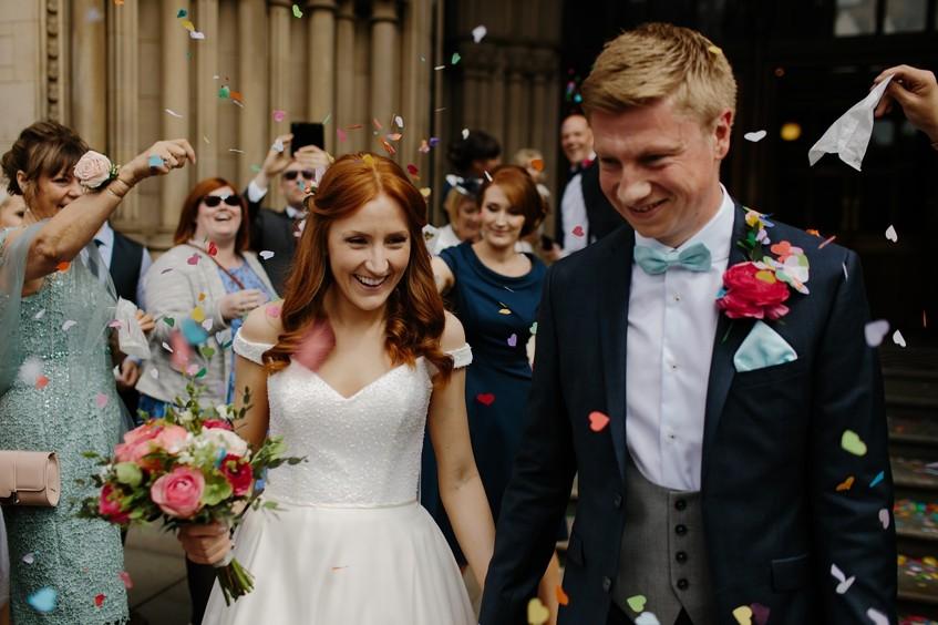 Ženich a nevěsta v záplavě konfet - to je pouťová barevná svatba.