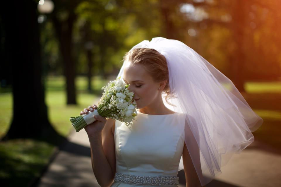 Krásná nevěsta se svatební kyticí z bledulí.