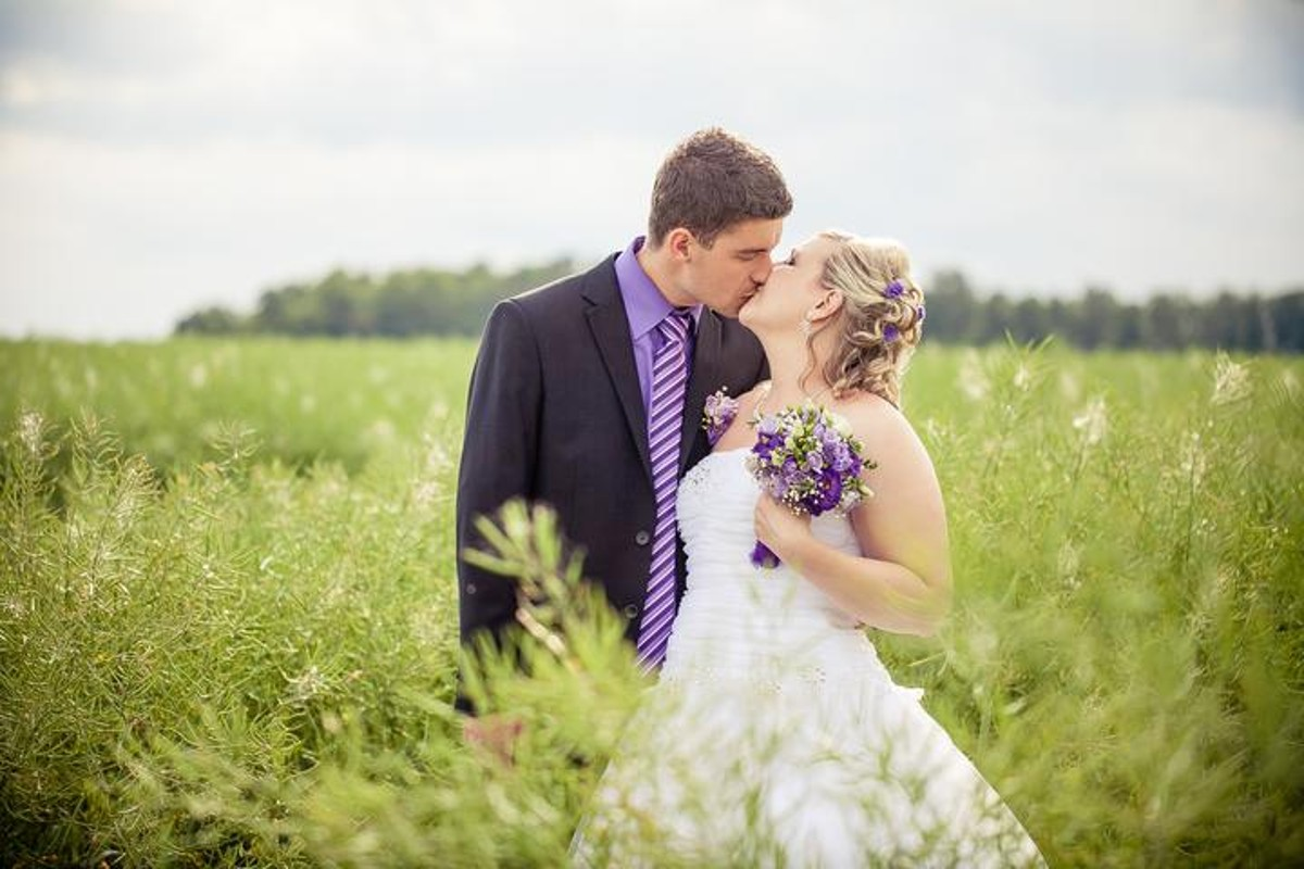 Ženich a nevěsta uprostřed polí.