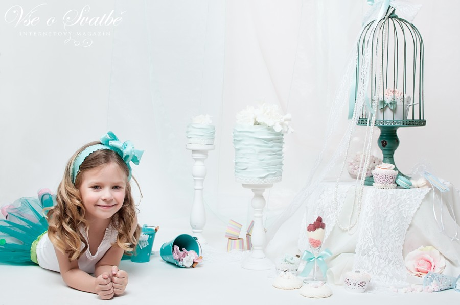 Malá holčička v tylové sukni s tyrkisovými dorty a dobrotami.