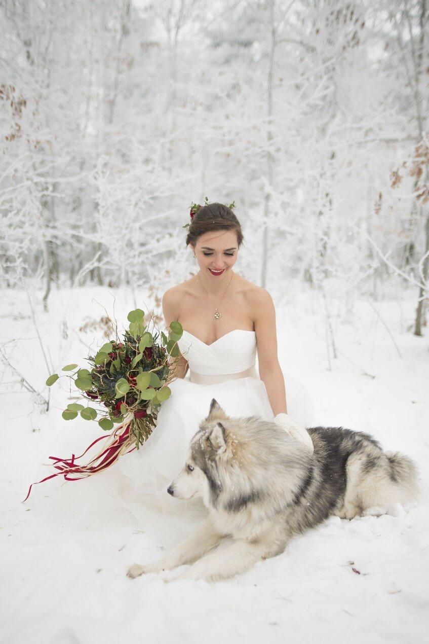 Nevěsta se svatební kyticí klečí u huskyho uprostřed zimy.