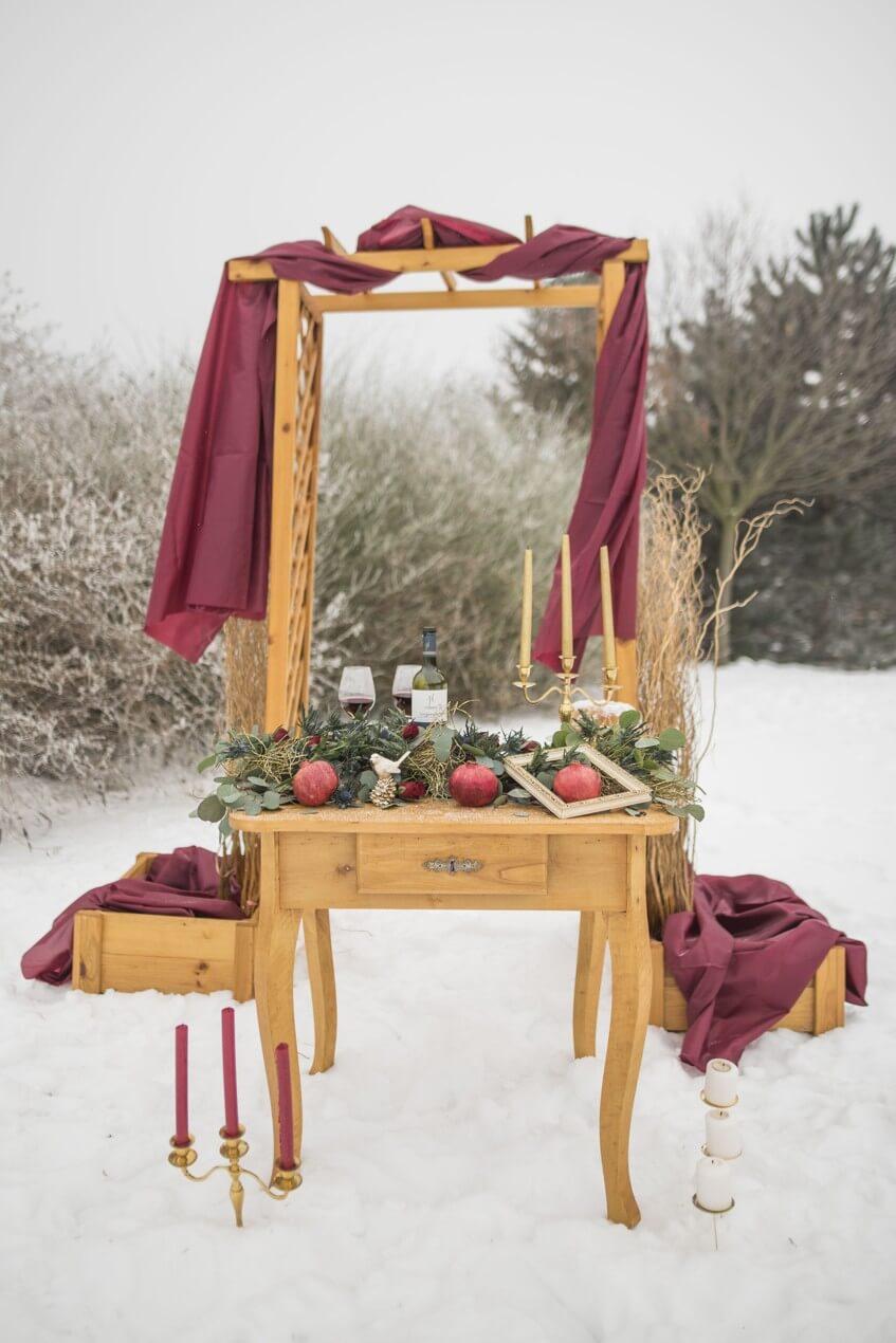 Originální slavobrána a vintage dřevěný stůl na zimní svatbě.