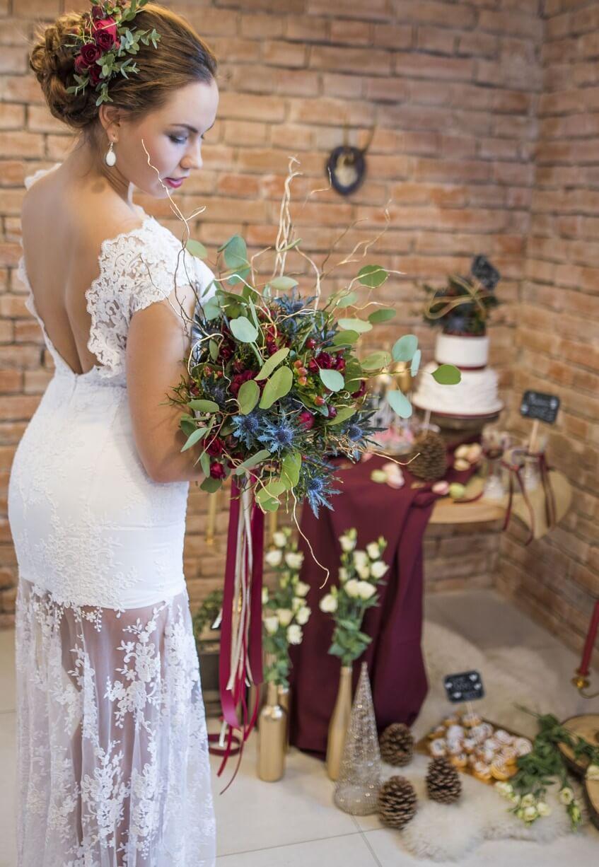 Nevěsta před cihlovou zdí s květinovou dekorací ve vlasech.