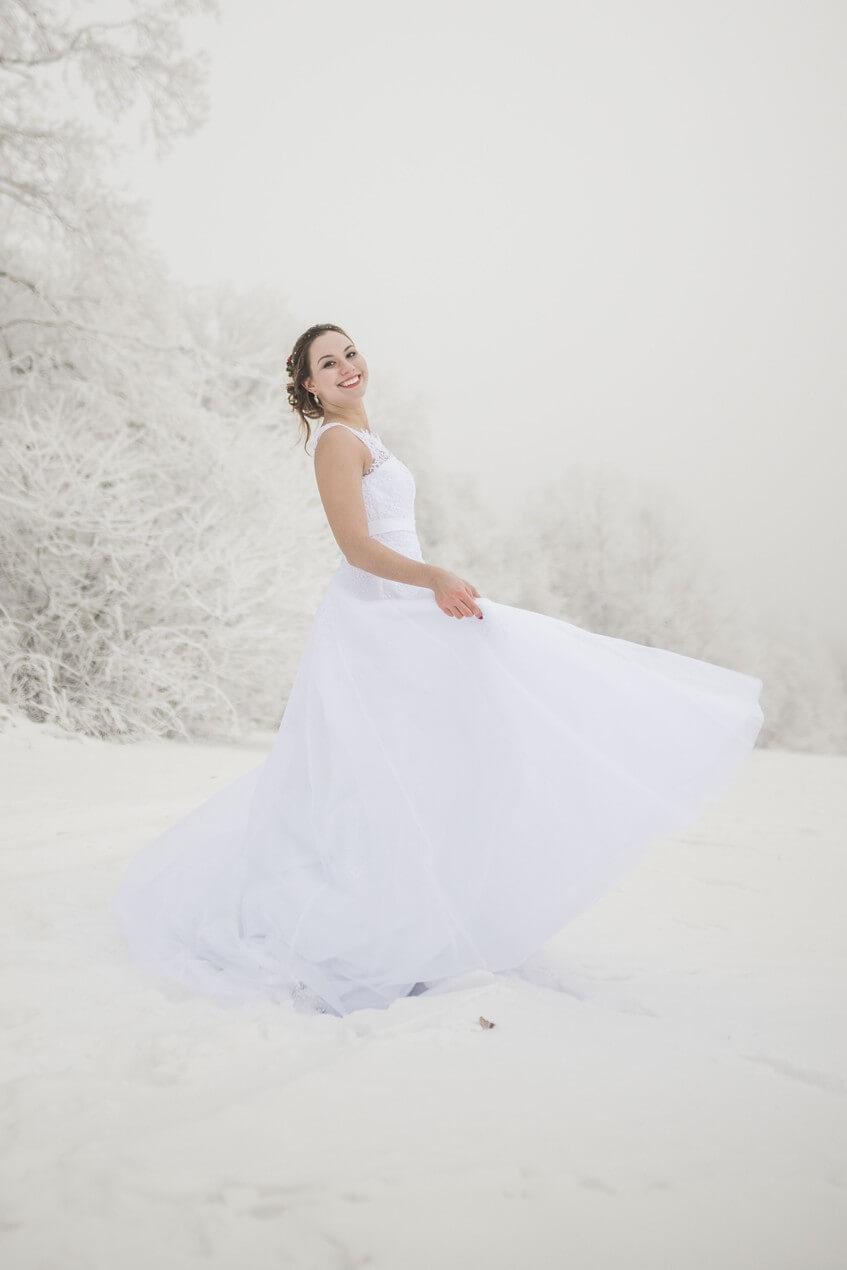 Rozesmátá nevěsta na sněhu.