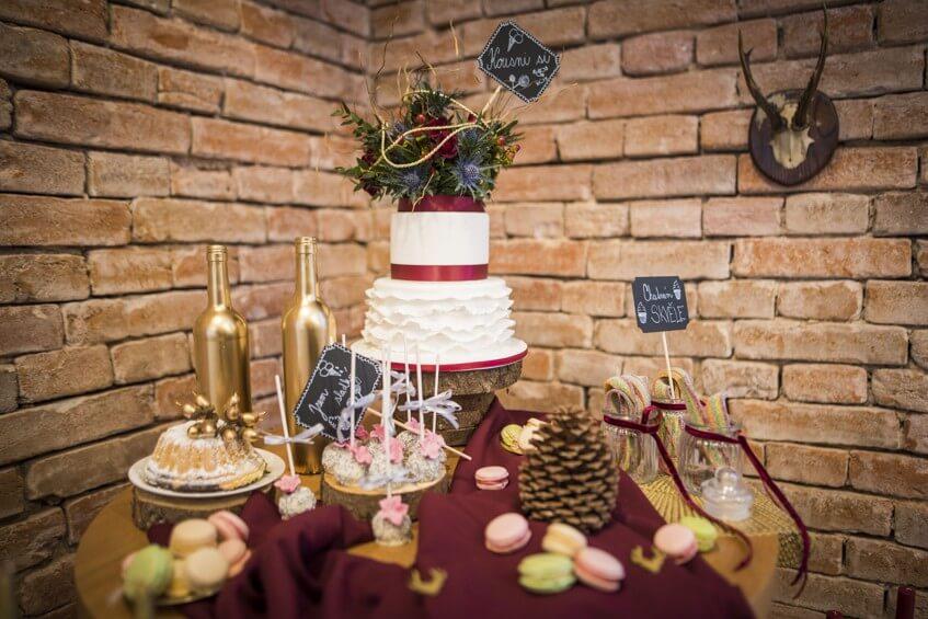 Sweet bar a svatebni dort se zlatými detaily a bordó doplňky.