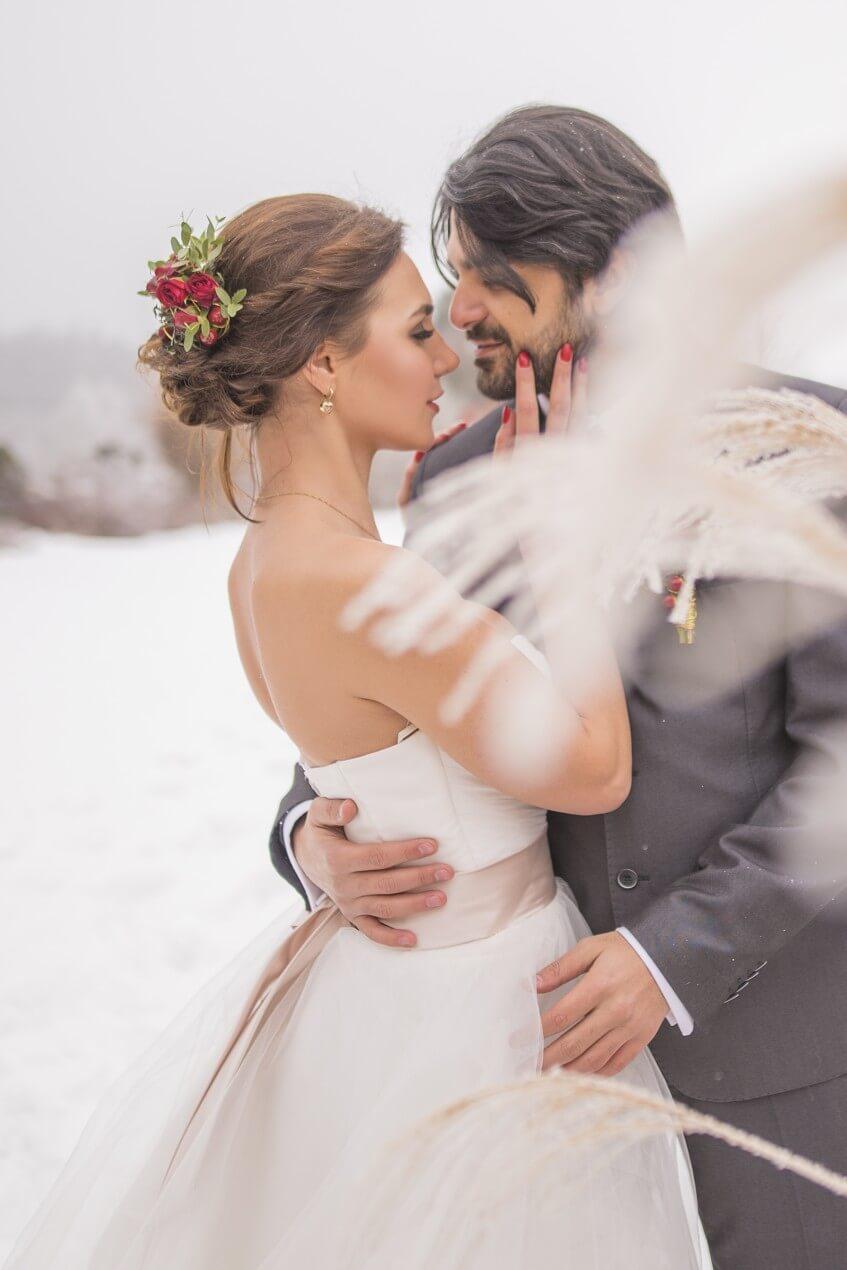 Romantický moment mezi ženichem a nevěstou na sněhu.