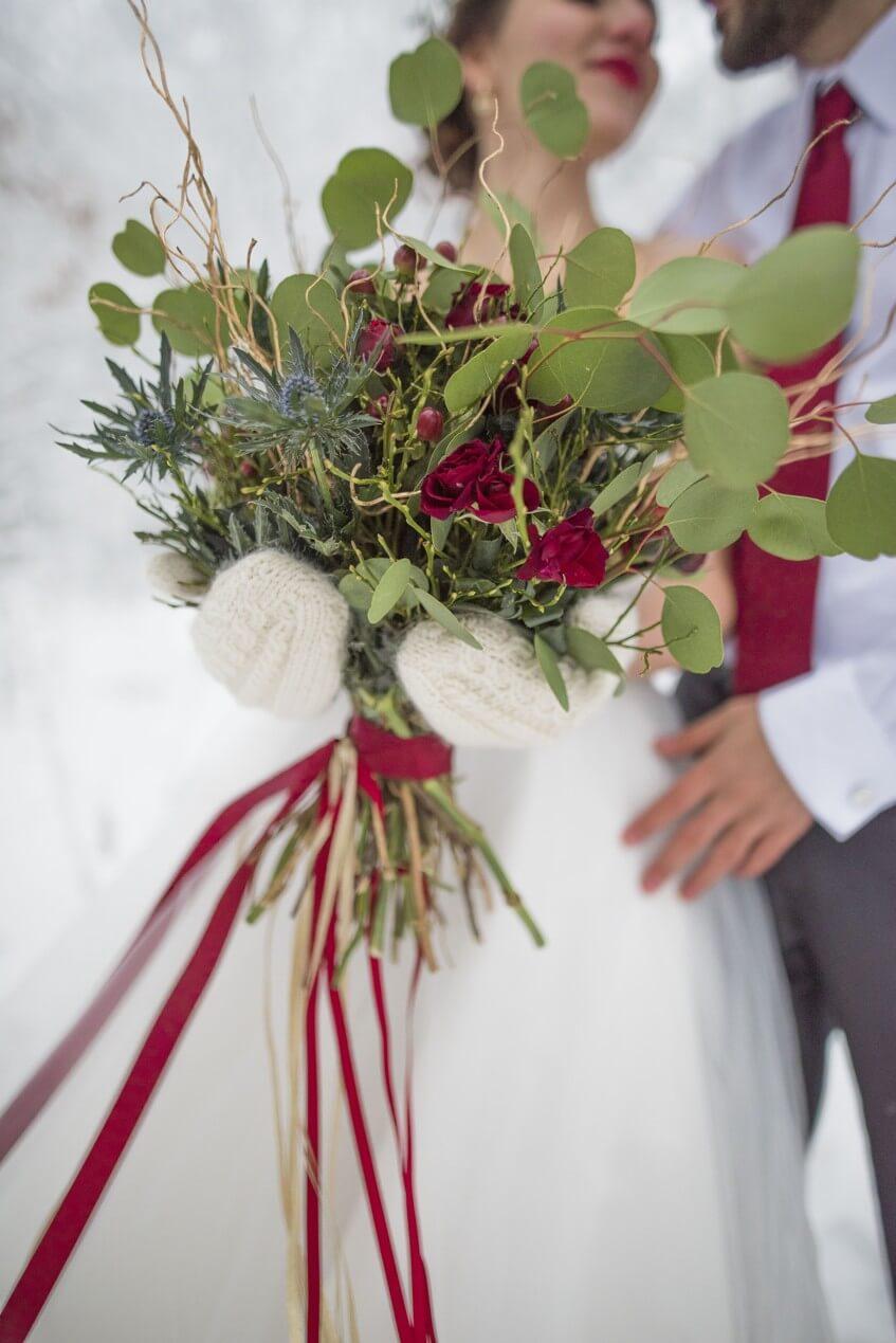 Zimní svatební kytice s rudými růžemi a bodláky.