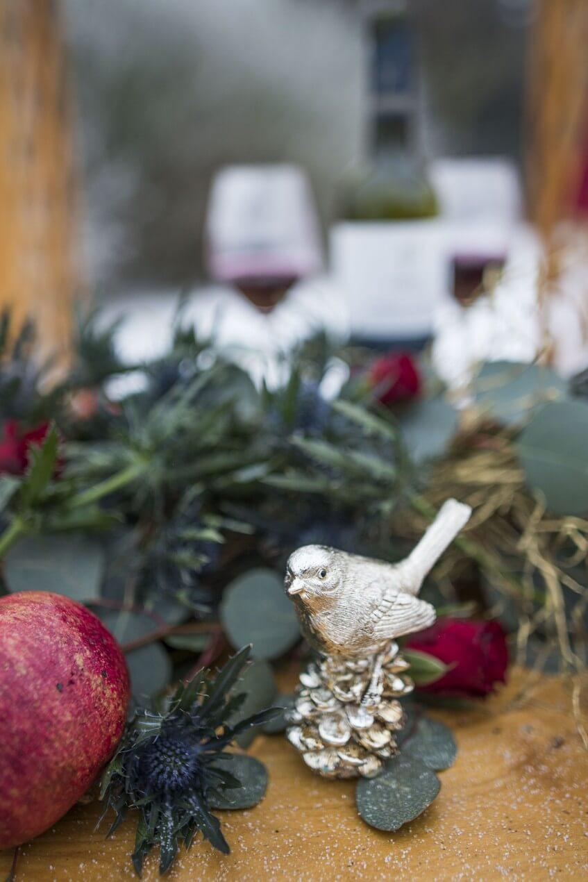 Zlatá dekorace ptáčka mezi granátovými jablky a bodláky.