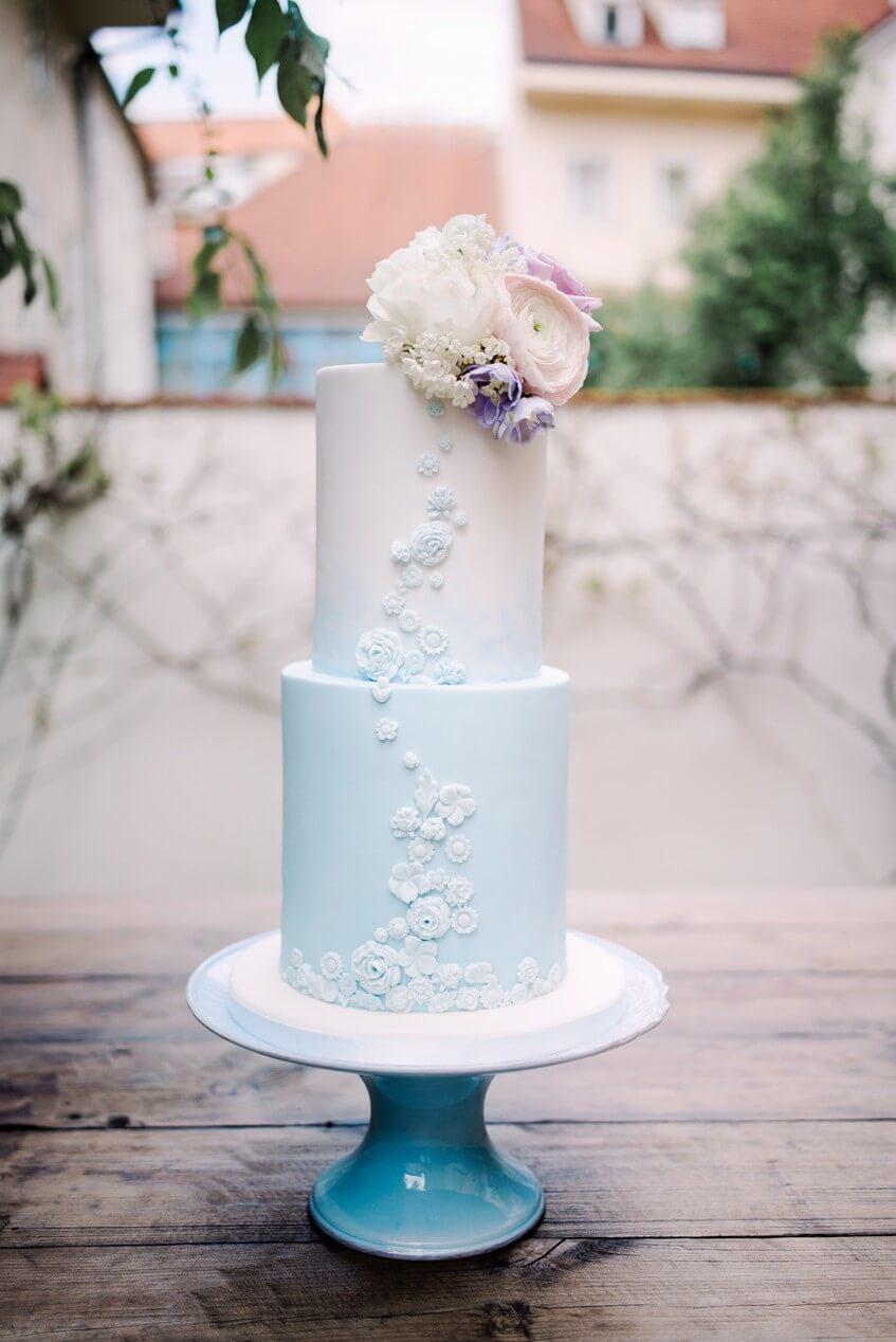 Bledě modrý dvoupatrový svatební dort s 3D kytičkami.