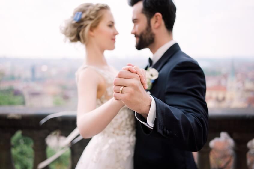 Novomanželé na balkoně nad městem.