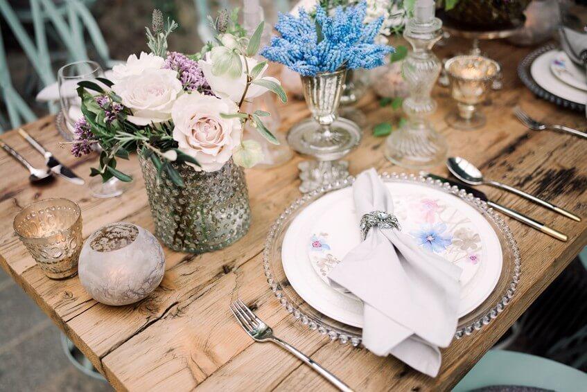 Svatební výzdoba v modré a růžové na dřeveném stole.
