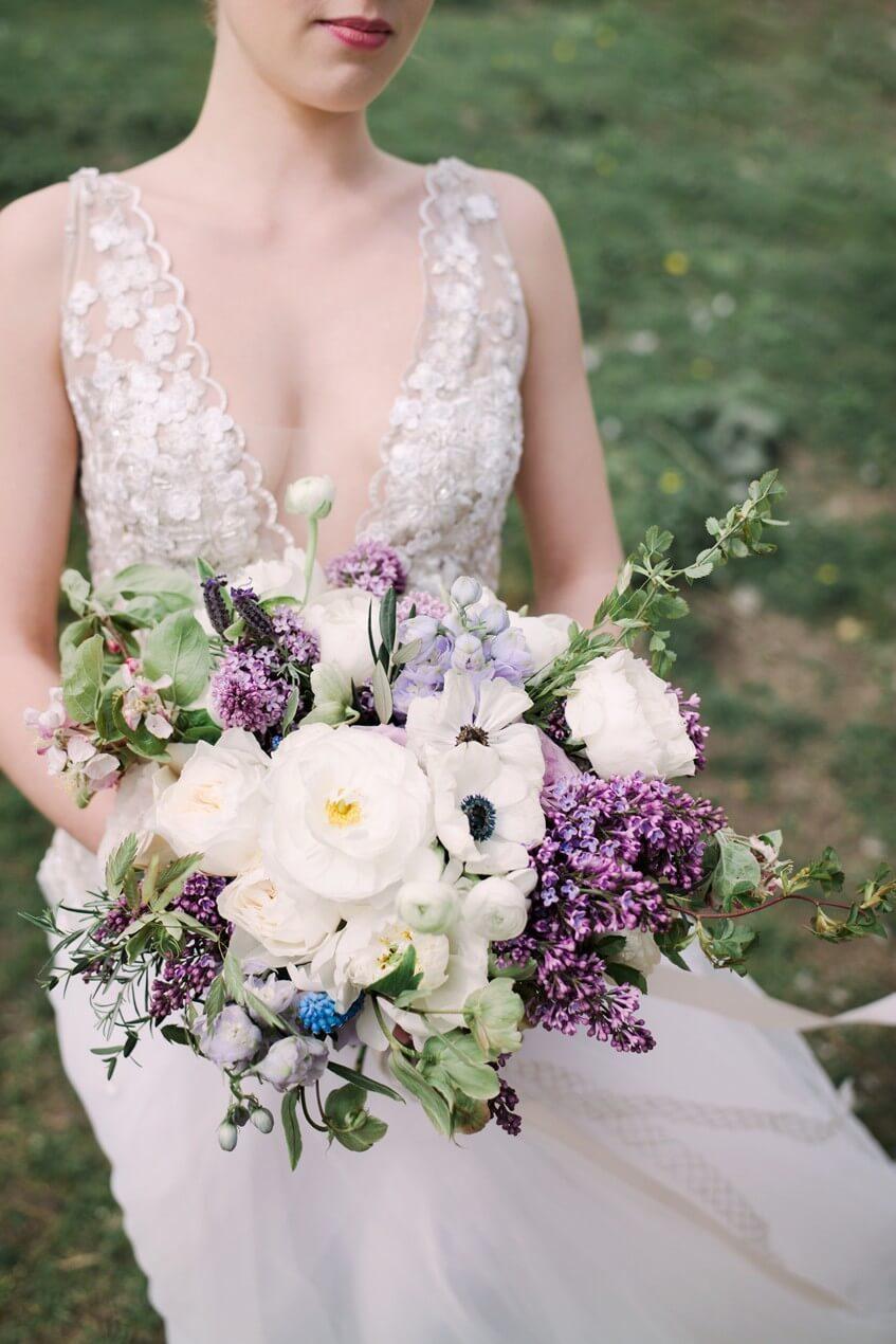 Svatební kytice z sasanek, šeříků, modřenců a růží.