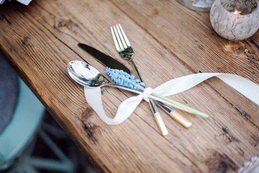 Zlato-stříbrné moderní příbory na svatebním stole.