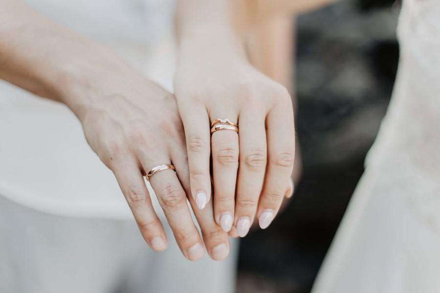 Detail rukou se snubními prstýnky.