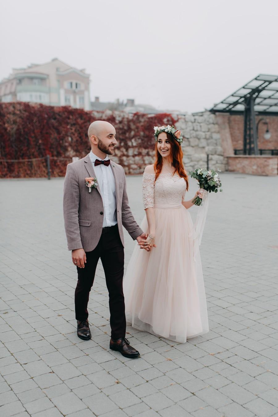 Netradiční ženich a nevěsta. Béžové sako, černé kalhoty a vínový motýlek.