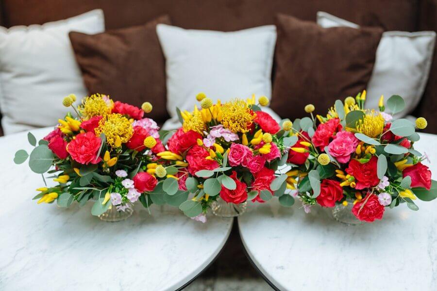 Květinové dekorace s růžemi a žlutými papričkami.